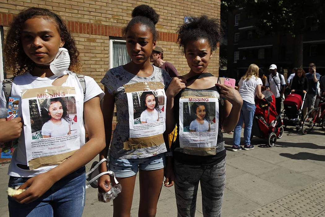 Girls have photos of a missing child on their T-shirts near the Grenfell Tower in London, Thursday, June 15, 2017. A massive fire raced through the 24-story high-rise apartment building in west Lo ...