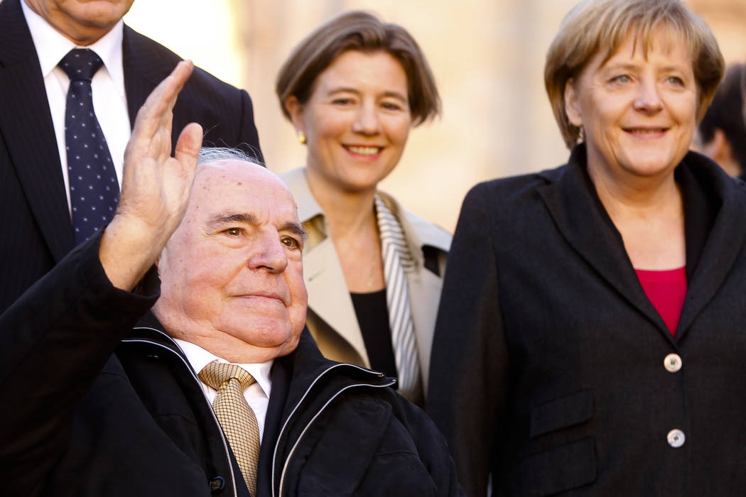 The Oct. 3, 2010 file photo shows former German Chancellor Helmut Kohl, left, waveing to audience as he arrives with his wife Maike Kohl-Richter, center, and Chancellor Angela Merkel, right, at th ...
