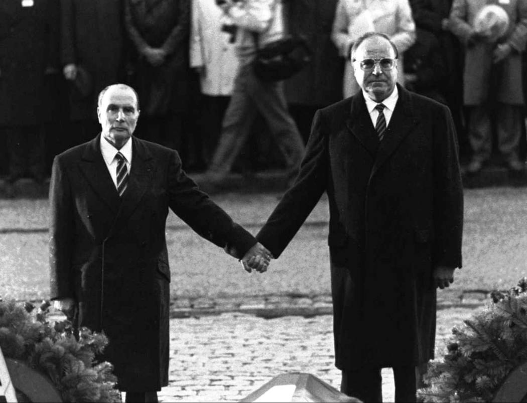 The Sept. 22, 1984 file photo shows then French President Francois Mitterrand and German Chancellor Helmut Kohl standing hand-in-hand as they listen to their respective national anthems during a F ...