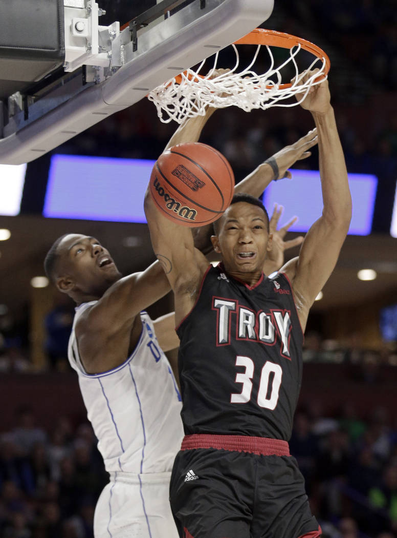 Troy's Alex Hicks (30) dunks against Duke's Harry Giles (1) during the first half in a first-round game of the NCAA men's college basketball tournament in Greenville, S.C., Friday, March 17, 2017. ...