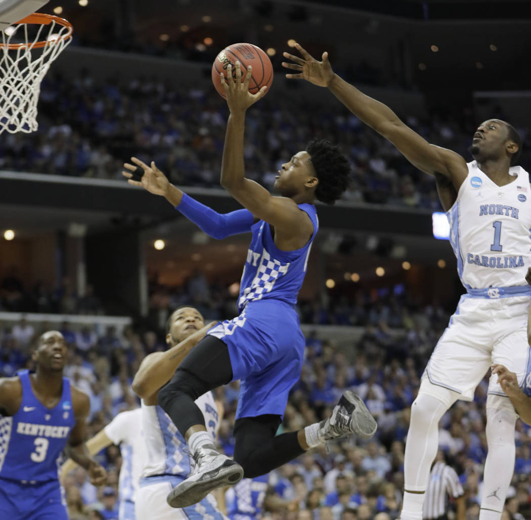 Kentucky guard De'Aaron Fox (0) shoots against North Carolina forward Theo Pinson (1) in the first half of the South Regional final game in the NCAA college basketball tournament Sunday, March 26, ...