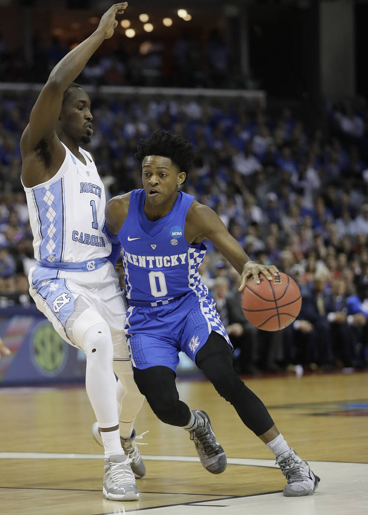 Kentucky guard De'Aaron Fox (0) moves past North Carolina forward Theo Pinson (1) in the first half of the South Regional final game in the NCAA college basketball tournament Sunday, March 26, 201 ...