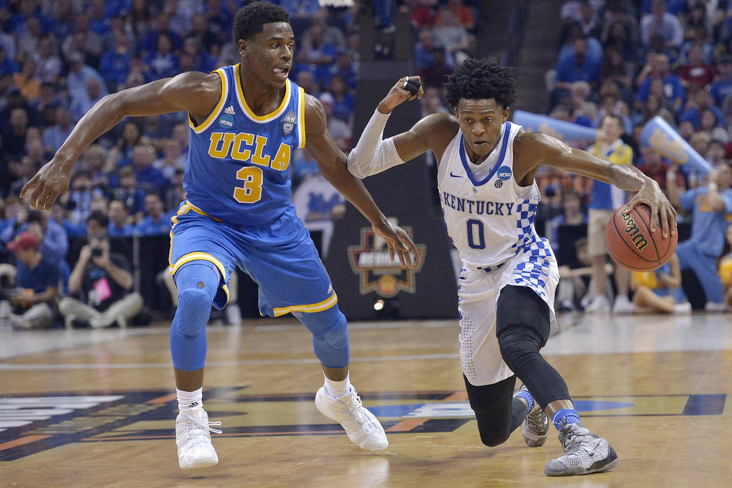 Kentucky guard De'Aaron Fox drives against UCLA guard Aaron Holiday in the second half of an NCAA college basketball tournament South Regional semifinal game Friday, March 24, 2017, in Memphis, Te ...