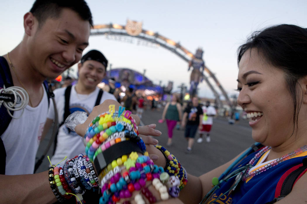 Darren Thephavongsa from San Jose, Calif. and Amanda Kaku from San Francisco exchange kandi on the first night of Electric Daisy Carnival at Las Vegas Motor Speedway on Friday, June 16, 2017 in La ...