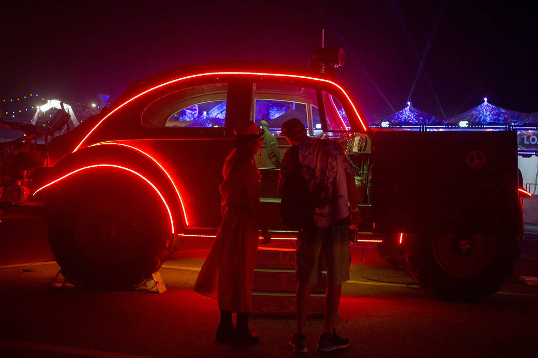 A reconstructed vehicle lights up behind a pair of attendees on the first night of Electric Daisy Carnival at Las Vegas Motor Speedway on Friday, June 16, 2017 in Las Vegas. Bridget Bennett Las Ve ...