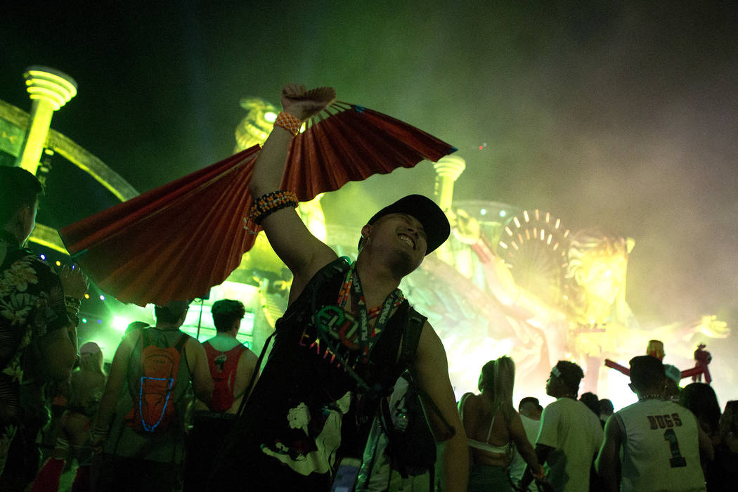 Dailmer Sena from San Francisco fans attendees as they walk past him at Kinetic Field on the first night of Electric Daisy Carnival at Las Vegas Motor Speedway on Friday, June 16, 2017 in Las Vega ...
