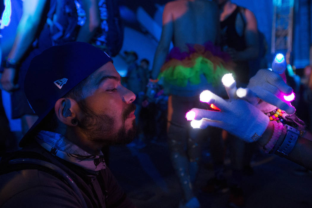 Attendee Andrew Castellanos  watches another attendee, Jeremy Wardle's gloves as they light up on the second night of Electric Daisy Carnival at Las Vegas Motor Speedway on Sunday, June 18, 2017 i ...