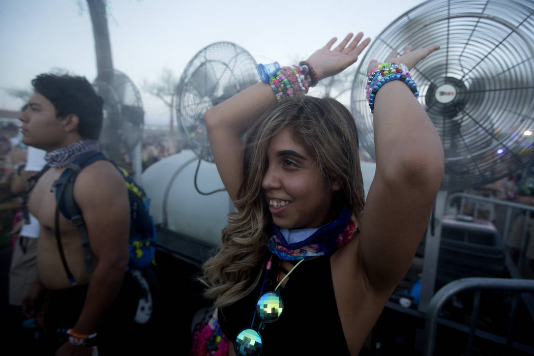 Rosa Mora from Lubbock, Texas stands in front of fan misters at the start of the last night of Electric Daisy Carnival at Las Vegas Motor Speedway on Sunday, June 18, 2017 in Las Vegas. Temperatur ...