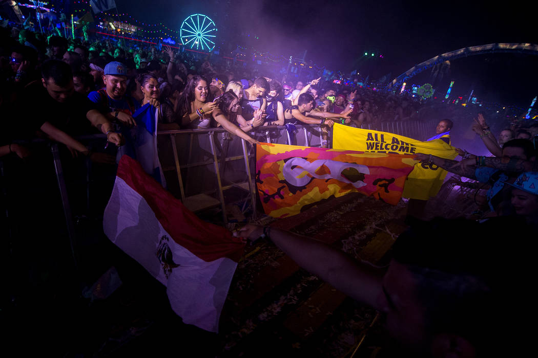 Attendees throw flags across the barrier while they enjoy Diplo, Jauz and Alison Wonderland's collaborative set at Kinetic Field on the last night of Electric Daisy Carnival at Las Vegas Motor Spe ...