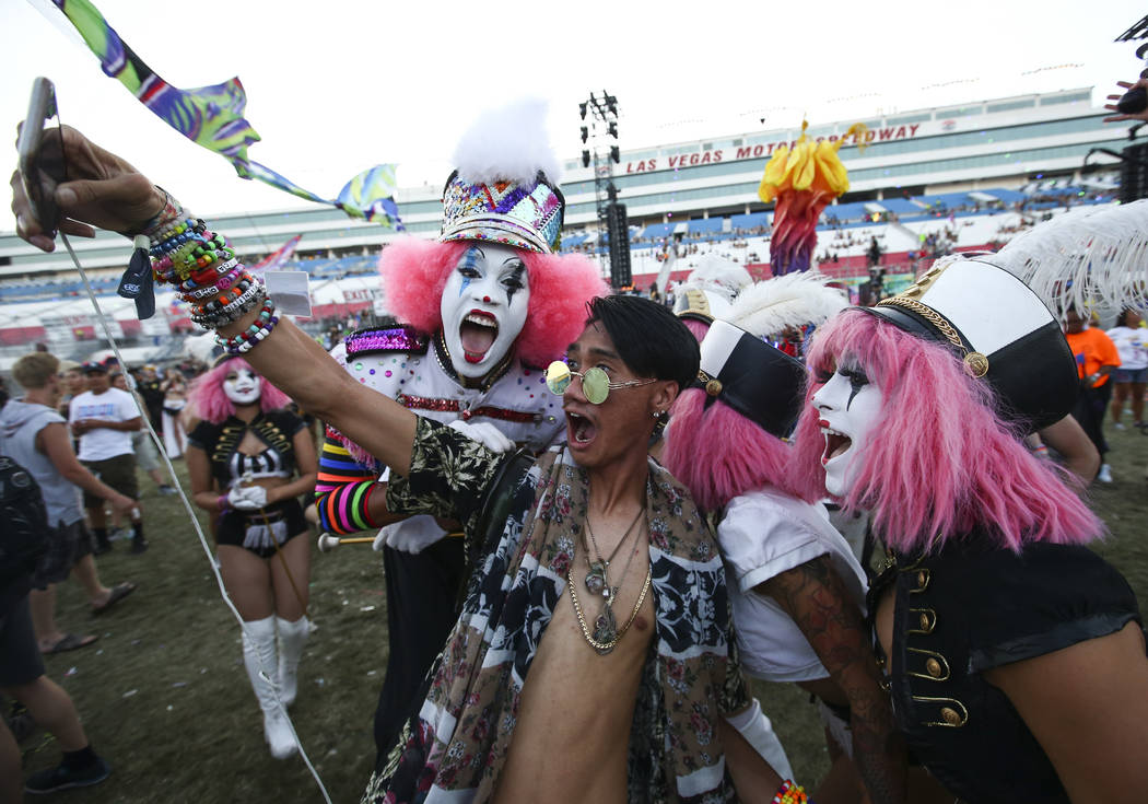 Alexander Nguyen of Los Angeles takes a selfie with costumed performers during the last day of the Electric Daisy Carnival at the Las Vegas Motor Speedway on Sunday, June 18, 2017. Chase Stevens L ...