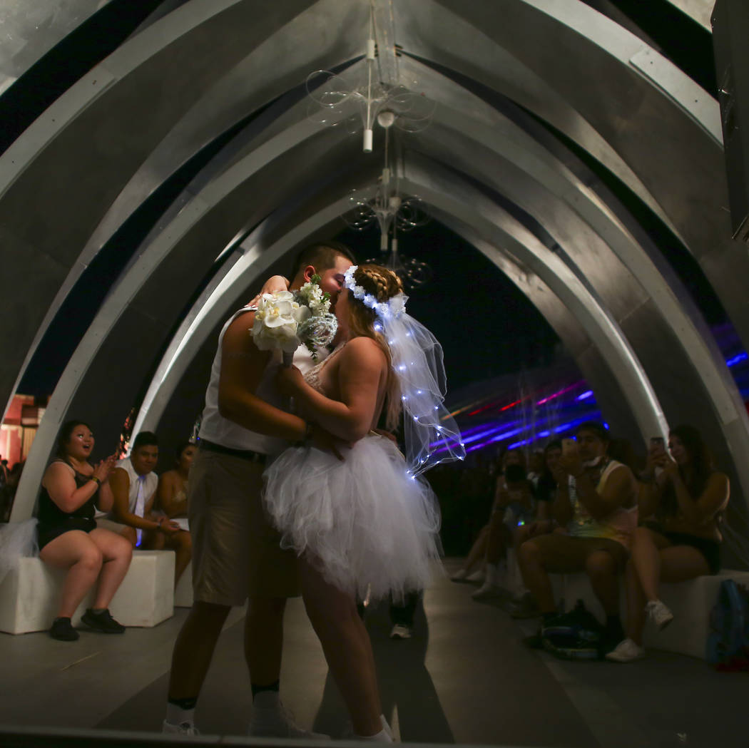 Homero Sandoval, left, and Ashli, both of Salt Lake City, Utah, kiss during their wedding ceremony on the last day of the Electric Daisy Carnival at the Las Vegas Motor Speedway on Sunday, June 18 ...