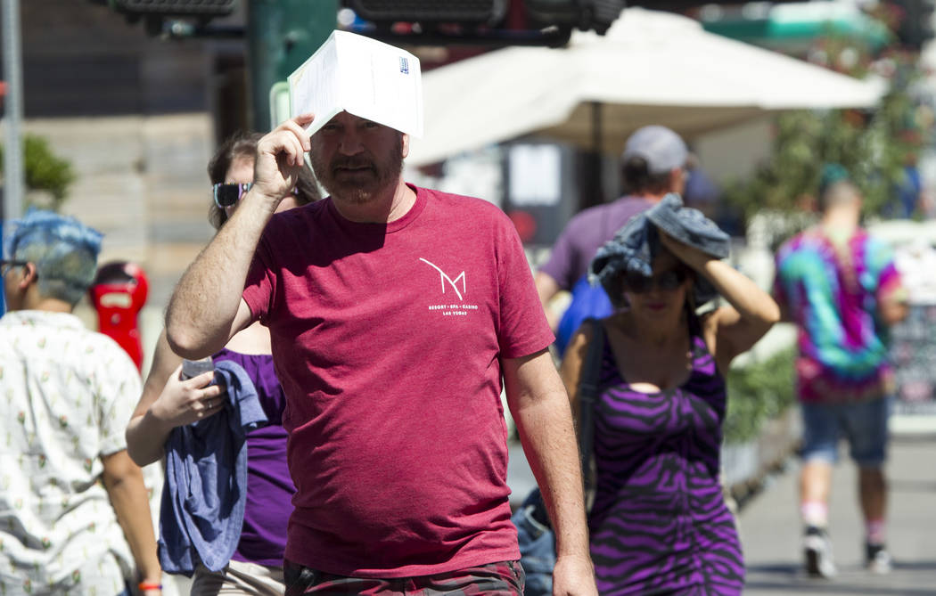 Pedestrians try to shield themselves from the sun as they walk along East Fremont Street in downtown Las Vegas on Saturday, June 17, 2017. Richard Brian Las Vegas Review-Journal @vegasphotograph