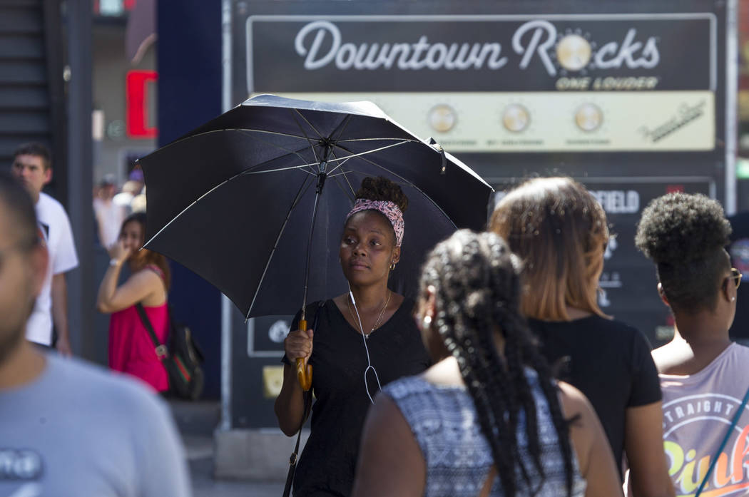 A woman carries an umbrella to protect herself from the sun as she walks along Fremont Street in downtown Las Vegas on Saturday, June 17, 2017. Richard Brian Las Vegas Review-Journal @vegasphotograph