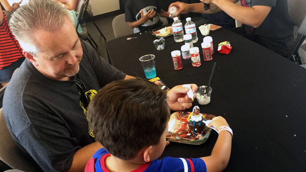 Jim Anderson and his 4-year-old son, Gavin, decorate a superhero cupcake during Superhero Day at the Downtown Container Park on Saturday. (Briana Erickson/Briana Erickson/Las Vegas Review-Journal)