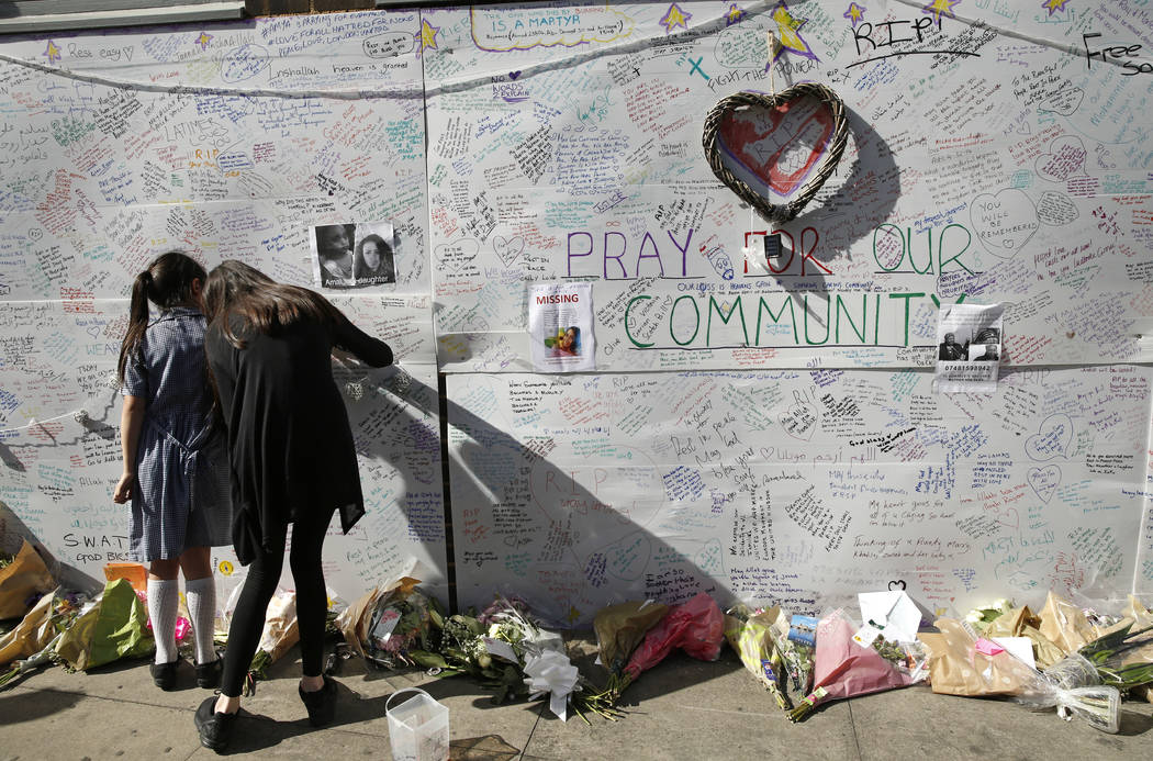People write messages on a wall for the victims and in support for those affected by the massive fire in Grenfell Tower, in London, Thursday, June 15, 2017. A massive fire raced through the 24-sto ...