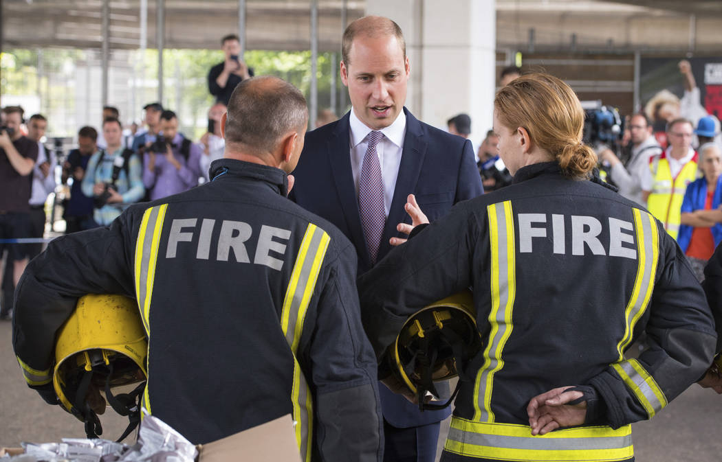 Britain's Prince William meets firefighters during a visit to the Westway Sports Centre which is providing temporary shelter for those who have been made homeless by the fire at Grenfell Tower,  i ...