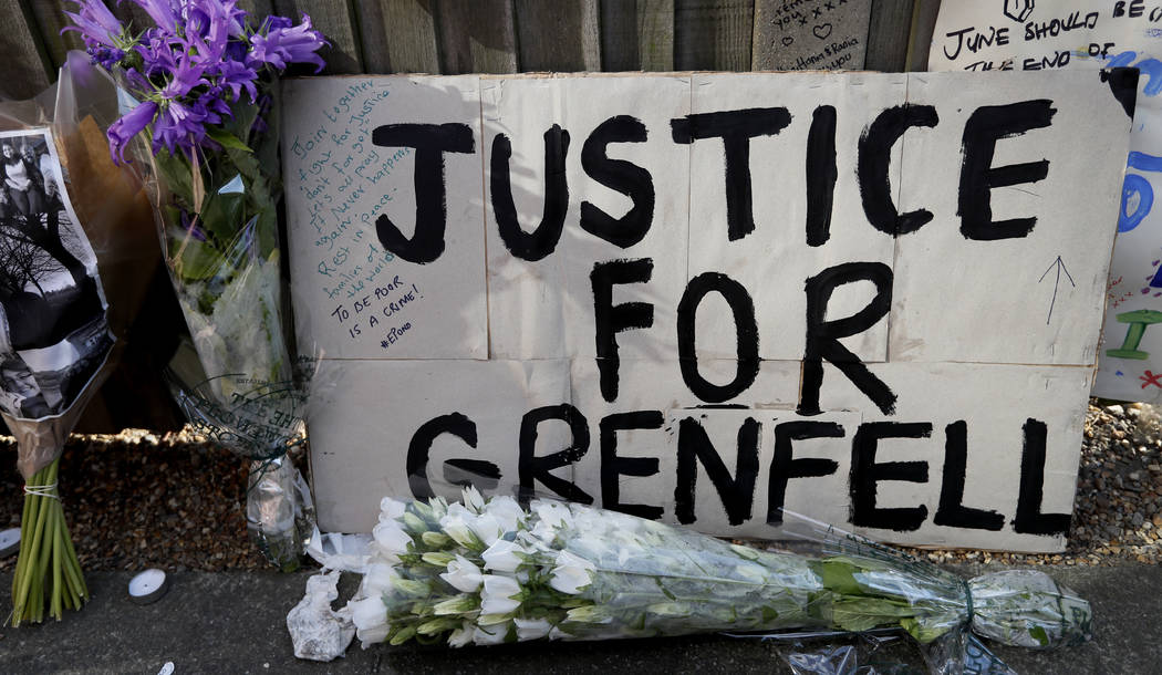 A poster and flowers are left near Grenfell Tower in London, Saturday, June 17, 2017. Police Commander Stuart Cundy said Saturday it will take weeks or longer to recover and identify all the dead  ...