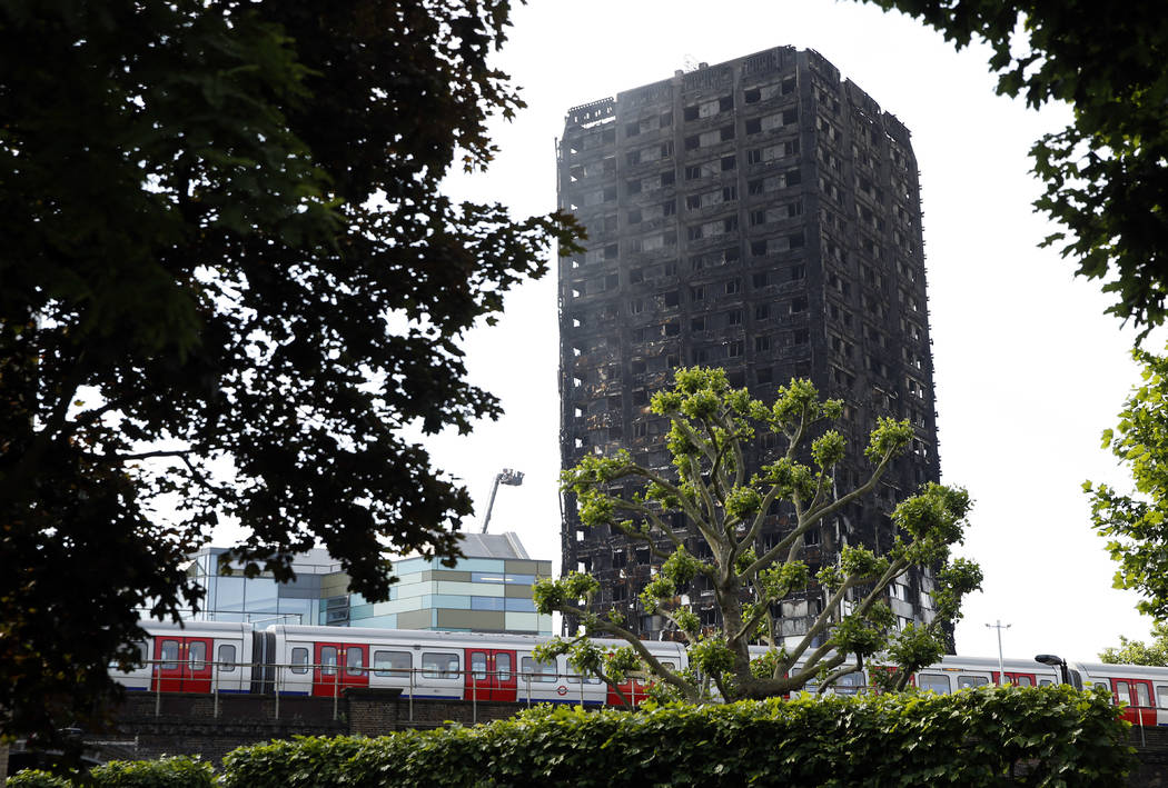 Tube trains run past the charred remains of Grenfell Tower, in London, Thursday, June 15, 2017. A massive fire raced through the 24-story high-rise apartment building in west London early Wednesda ...