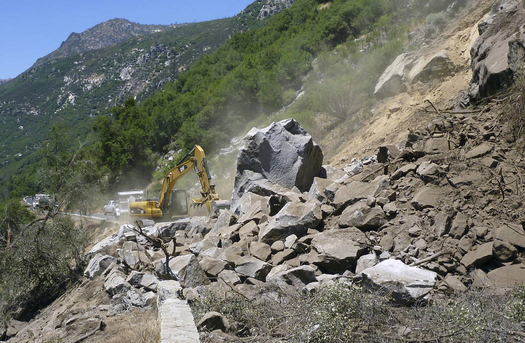 Workers clear El Portal Road in Yosemite National Park, Calif. The rockslide, which came crashing down Monday at Yosemite National Park is creating a commuting headache for hundreds of park employ ...