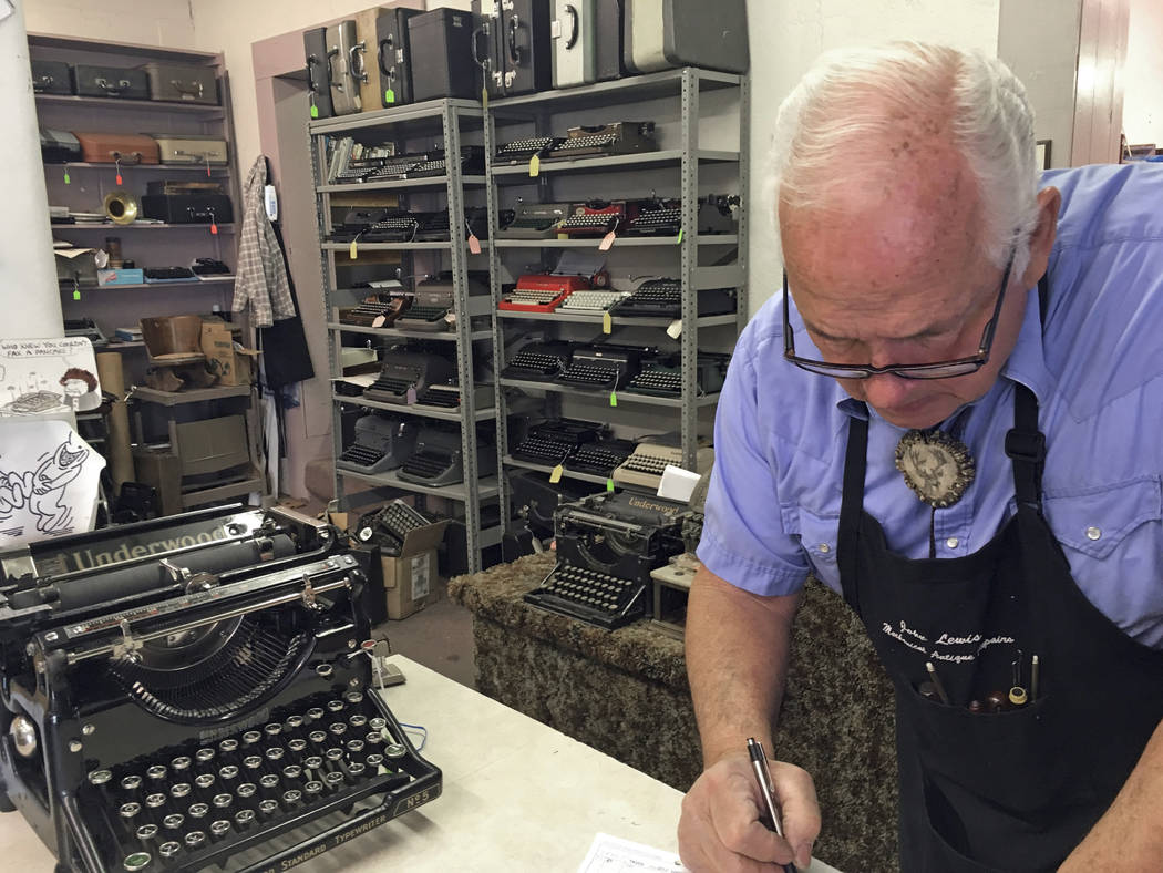 John Lewis, a typewriter repairman, works at his shop in Albuquerque, N.M., in front of his collection of vintage typewriters in January. (AP Photo/Russell Contreras)