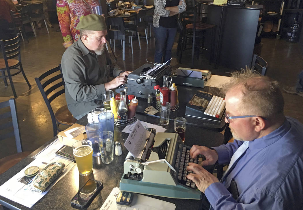 "Joe Van Cleave, left, and Rich Boucher, right, try out various vintage typewriters at a ""type-in"" in Albuquerque, N.M., in April.  (AP Photo/Russell Contreras)"