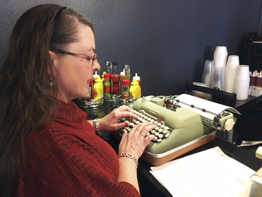 "Andrea Kittle, of Albuquerque, N.M., tries out a vintage Smith Corona electric typewriter at a ""type-in"" in Albuquerque in April.  (AP Photo/Russell Contreras)"