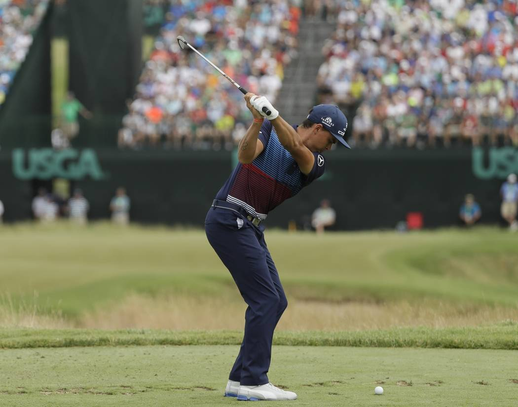 Rickie Fowler hits a shot from the ninth tee during the third round of the U.S. Open golf tournament Saturday, June 17, 2017, at Erin Hills in Erin, Wis. (AP Photo/David J. Phillip)