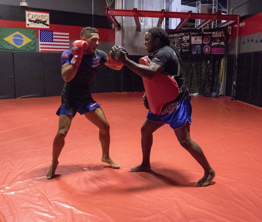 UFC lightweight Kevin Lee, left, trains for his five-round fight at UFC Fight Night 112 hitting mitts with his striking coach Dewey Cooper at One Kick's Gym in Las Vegas, Tuesday, June 6, 2017. He ...