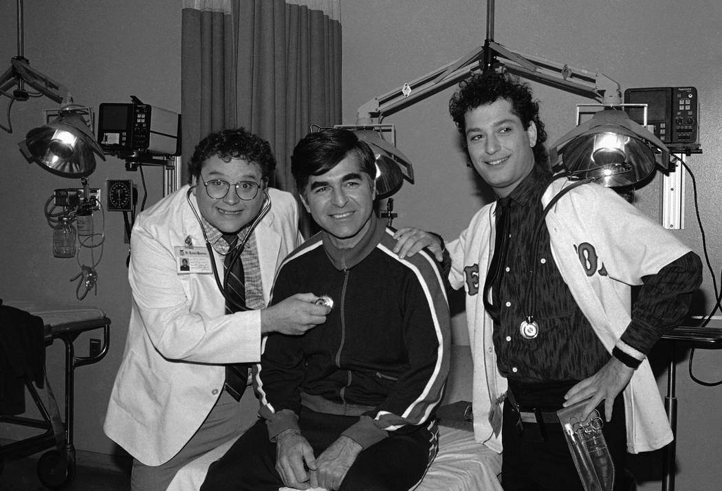 "In this Nov. 9, 1984, file photo, Massachusetts Gov. Michael Dukakis, center, receives treatment from Stephen Furst, left, and Howie Mandel, stars of NBC's television series ""St. Elsewhere,"" in Lo ..."