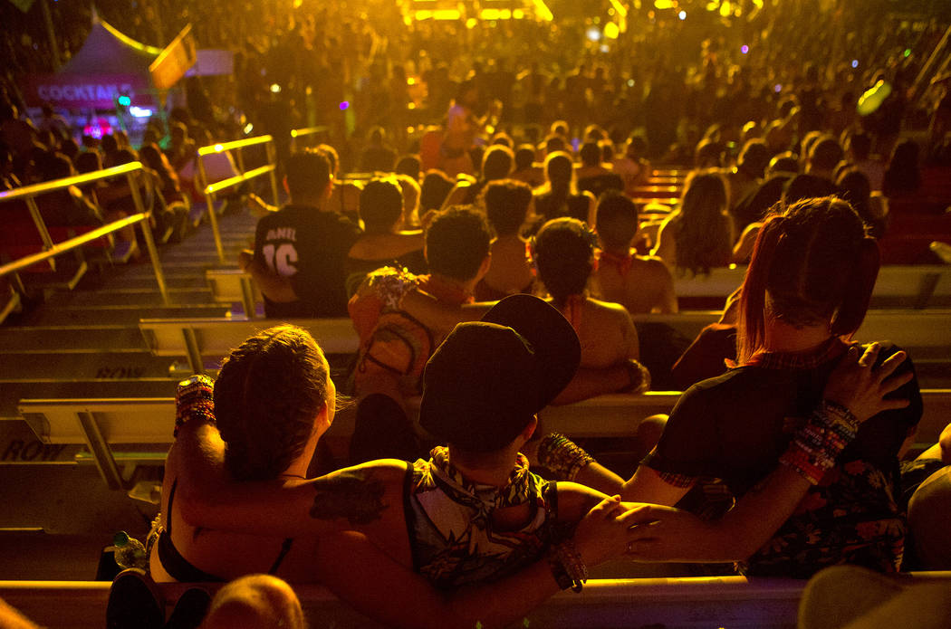 Attendees put their arms around one another in the stands during Major Lazer's set at Cosmic Meadows on the first night of Electric Daisy Carnival at Las Vegas Motor Speedway on Saturday, June 17, ...
