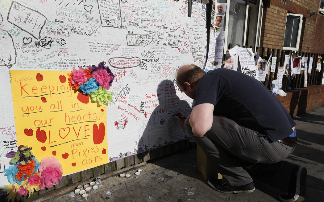 A man signs a message board placed near Grenfell Tower in London, Saturday, June 17, 2017. Police Commander Stuart Cundy said Saturday it will take weeks or longer to recover and identify all the  ...