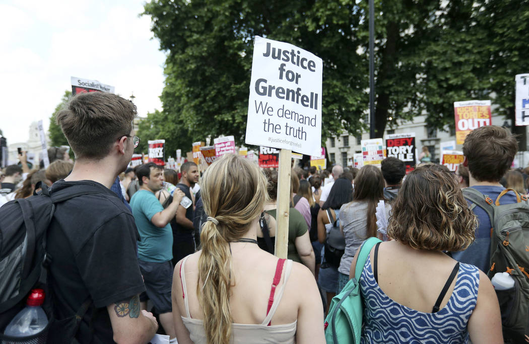 People gather in Whitehall, to protest after the fire at Grenfell Tower which engulfed the 24 storey building on Wednesday, in London, Saturday, June 17, 2017. More than 3 million pounds ($3.8 mil ...