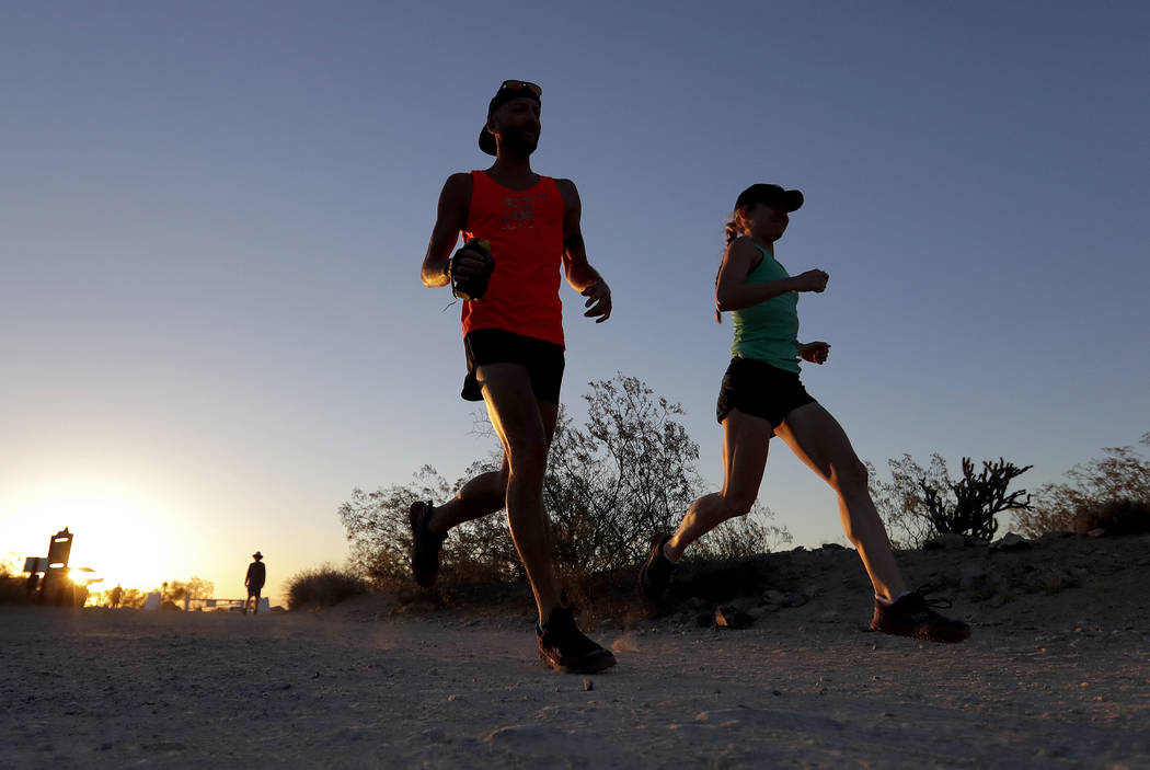 A couple runs through section of South Mountain Park at sunrise to avoid the excessive heat, Friday, June 16, 2017 in Phoenix. (AP Photo/Matt York)