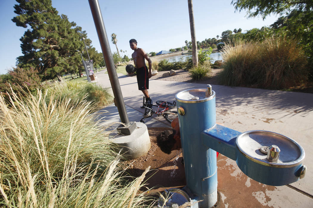 Marcuel Miller, 14, gets drink of water as Davion Hambrick, 16, watches at Lorenzi Park on Sunday, June 18, 2017, in Las Vegas. Rachel Aston Las Vegas Review-Journal @rookie__rae