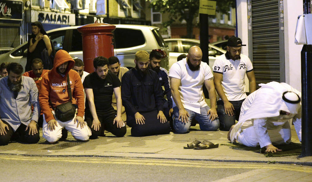 Local people observe prayers at Finsbury Park where a vehicle struck pedestrians in London Monday, June 19, 2017. Police say a vehicle struck pedestrians near a mosque in north London, leaving sev ...