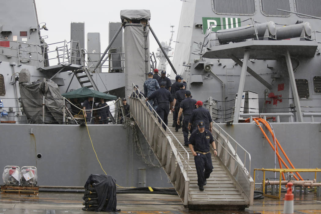 U.S. military personnel work on board the damaged USS Fitzgerald at the U.S. Naval base in Yokosuka, southwest of Tokyo Sunday, June 18, 2017. The search for seven U.S. Navy sailors missing after  ...