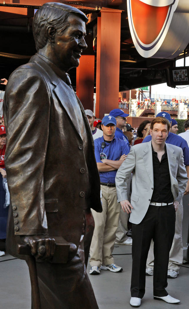 Kane Kalas, right, looks at the statue of his father, Hall-of-Fame broadcaster Harry Kalas, before a baseball game between the Philadelphia Phillies and the Arizona DiamondbacksTuesday, Aug. 16, 2 ...