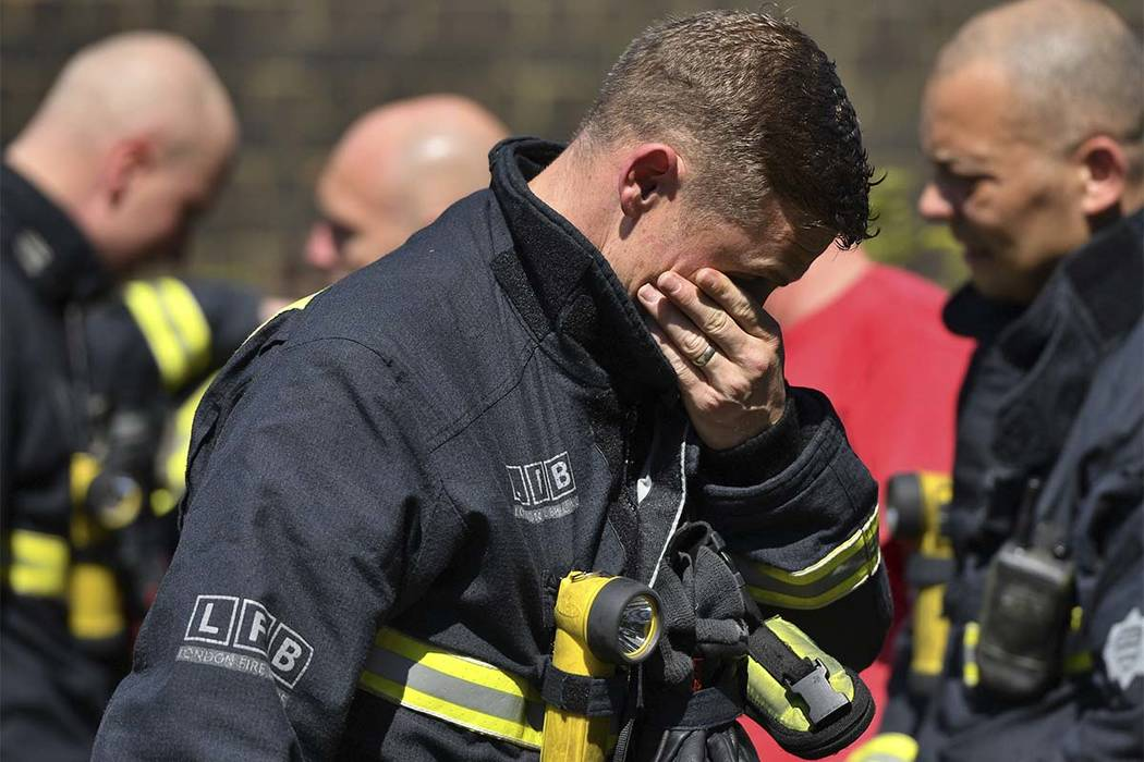 A firefighter puts his hand to his face as he looks at the floral tributes before a minute of silence for the victims of last week's fire in west London Monday, June 19, 2017. The death toll has c ...