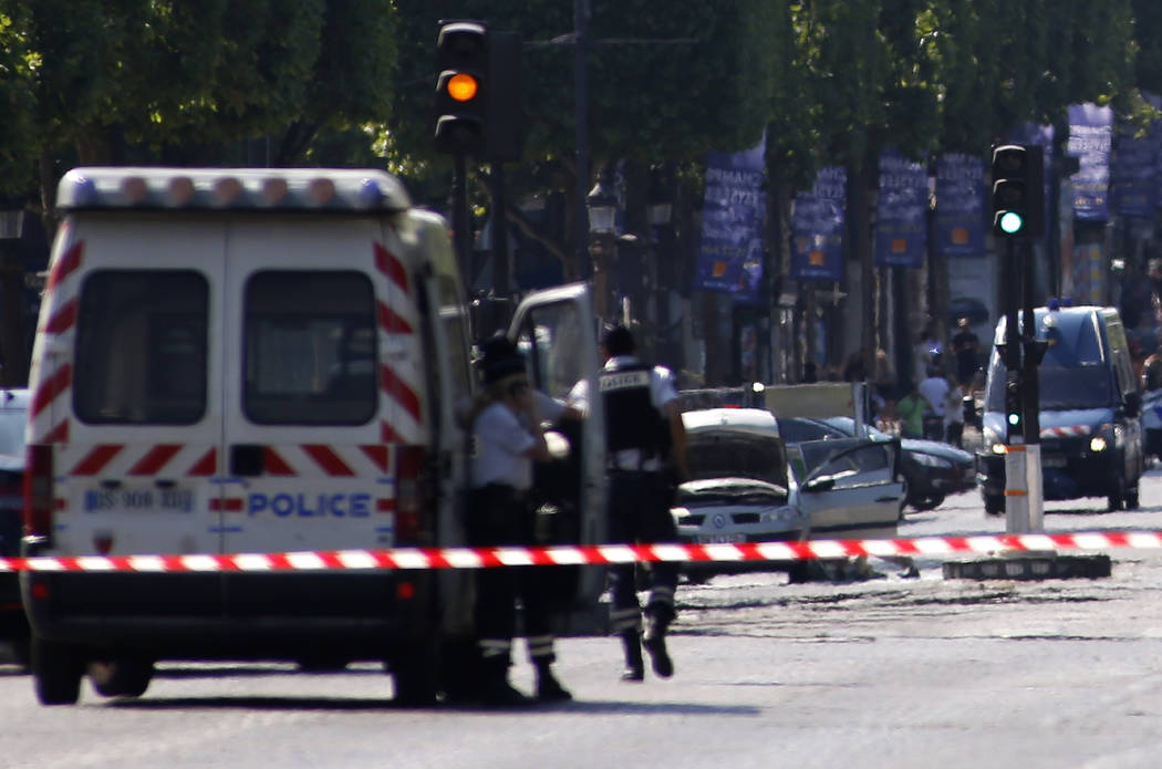 Police forces secure the area on the Champs Elysées next to the suspected car, center, in Paris, Monday, June 19, 2017. A man rammed his car into a police vehicle in Paris' Champs-Elysees shoppin ...