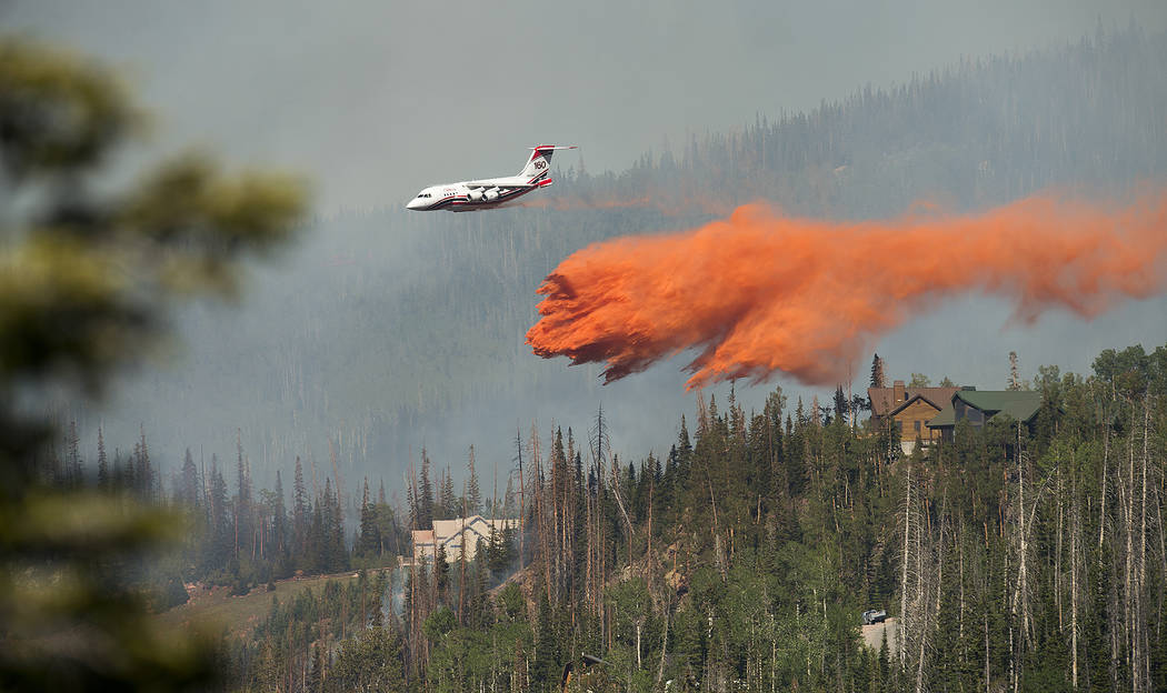 A plane drops fire retardant as a wildfire burns Sunday, June 18, 2017, along the Steam Engine area near the southern Utah ski town of Brian Head, Utah. Firefighters were hoping to have a blaze ne ...