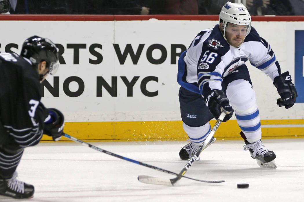 Winnipeg Jets center Marko Dano (56) of Austria looks to take a shot as New York Islanders defenseman Travis Hamonic (3) blocks it during the first period of an NHL hockey game, Thursday, March 16 ...