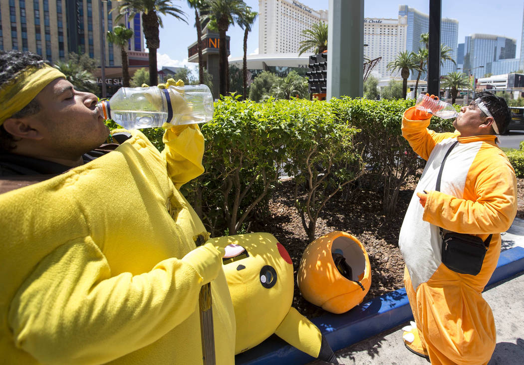 Street performers Ruben Osorio, left, and Raul Diaz take a break from posing for photos with tourists as Charmander and Pikachu along The Strip on Monday, June 19, 2017. Richard Brian Las Vegas Re ...