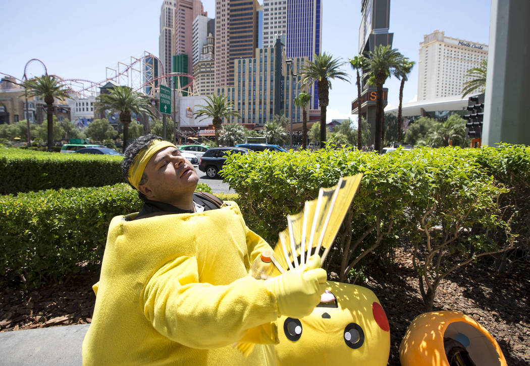 Street performer Ruben Osorio waves a fan to cool off as he takes a break from posing for photos with tourists as Pikachu along The Strip on Monday, June 19, 2017. Richard Brian Las Vegas Review-J ...