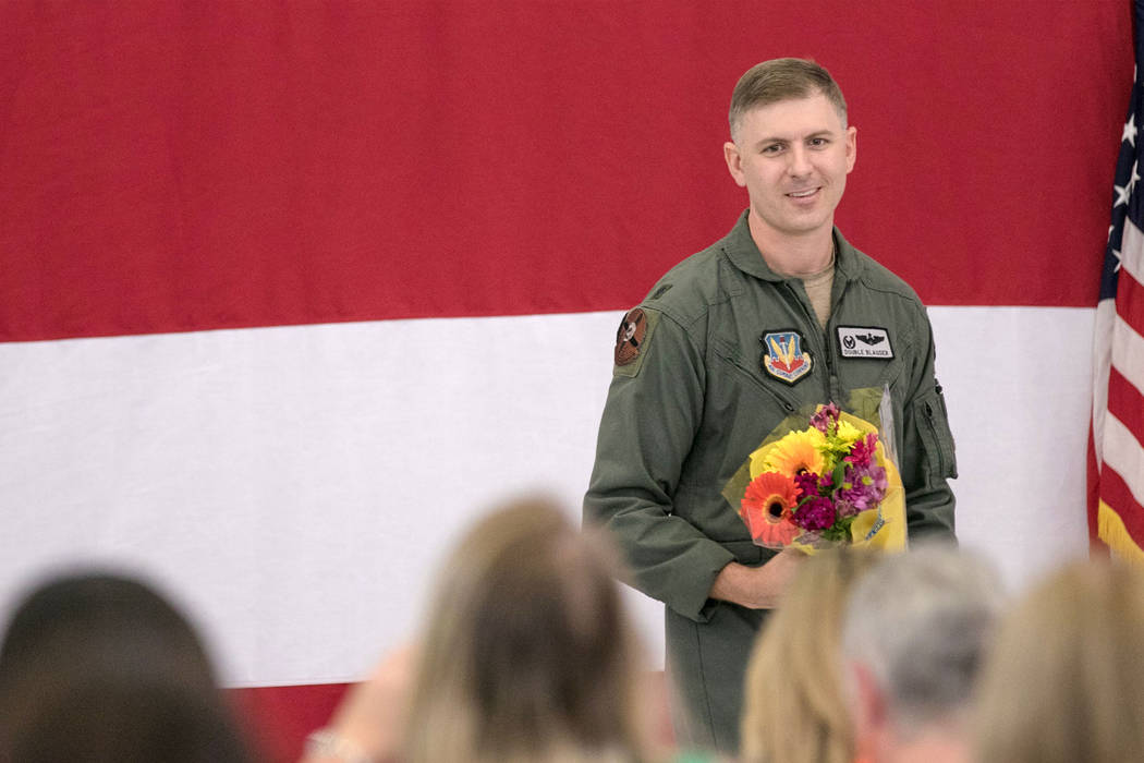 Lt. Col. Michael Blauser approaches his wife with a bouquet of flowers at Nellis Air Force Base during an activation ceremony of an F-35A Lightning II aircraft on Tuesday, June 21, 2017, in Las Ve ...
