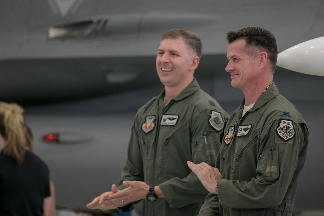 Lt. Col. Michael Blauser, left, and Col. Michael R. Drowley, right,  applaud at Nellis Air Force Base during an activation ceremony of an F-35A Lightning II aircraft on Tuesday, June 21, 2017, in  ...