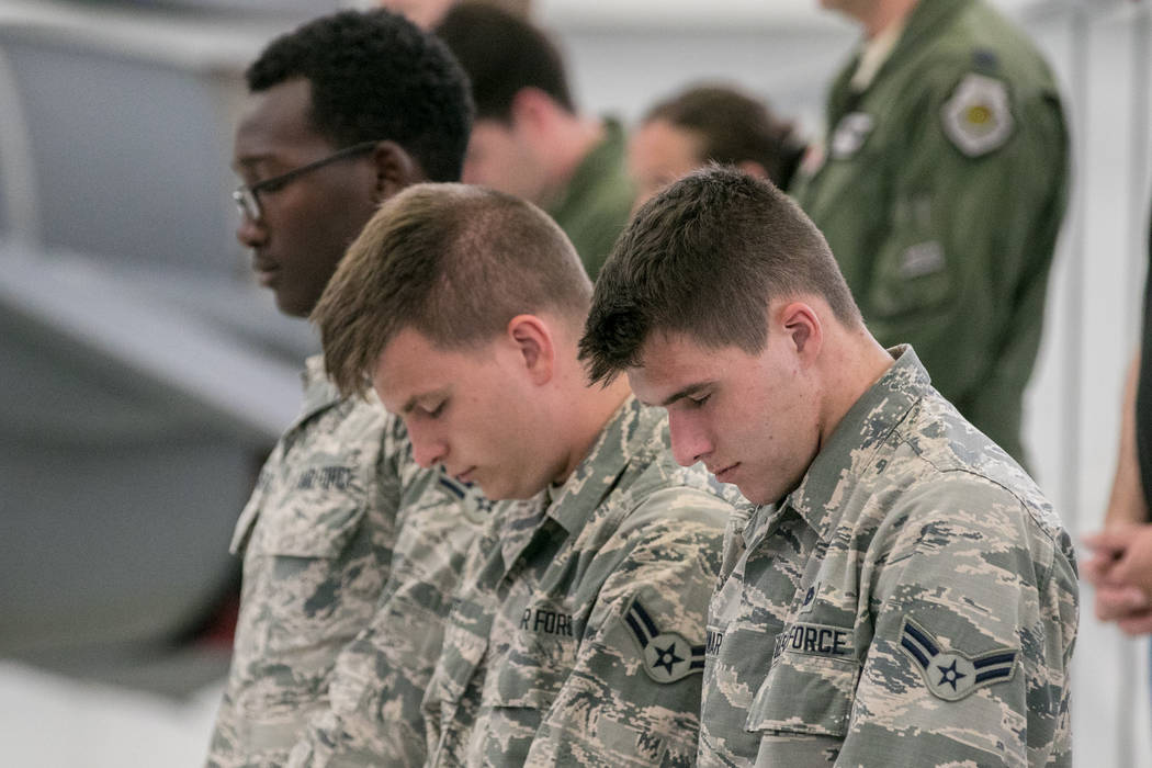Kalob Cowart, Devon Fife and Darquise Fullard-Green bow their heads in prayer at Nellis Air Force Base during an activation ceremony of an F-35A Lightning II aircraft on Tuesday, June 21, 2017, in ...
