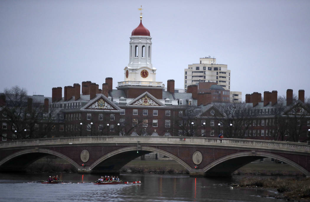 FILE - In this March 7, 2017 file photo, rowers paddle down the Charles River near the campus of Harvard University in Cambridge, Mass. A debate over the appropriateness of the school's decision t ...