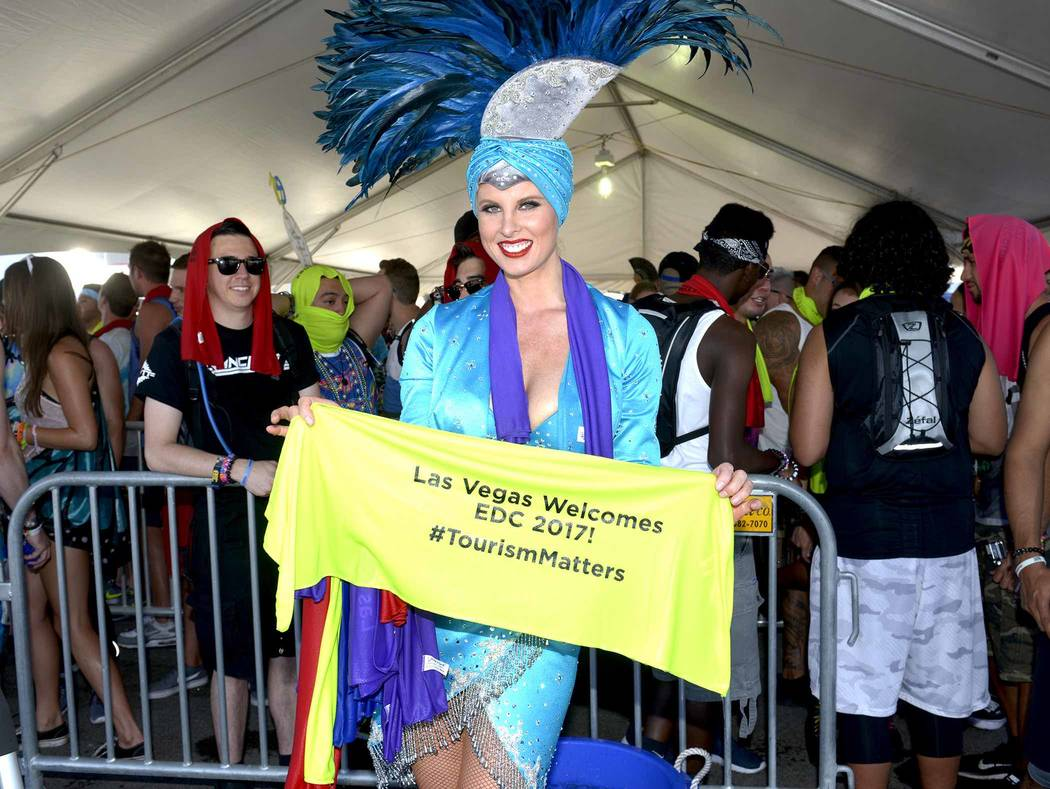 LVCVA Host Committee Brand Ambassador Showgirls give away cooling towels and bracelets to Electric Daisy Carnival fans waiting in line for the downtown shuttles to Day 1 of the EDC event at the  L ...