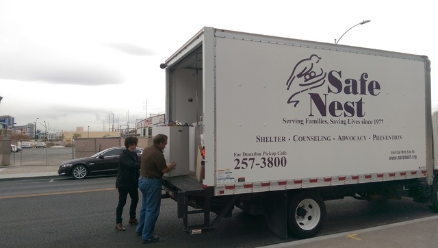 Parking Service employees help load a Safe Nest truck with donated toys. Mondays Dark is holding a fundraiser for the women's shelter at a community theater. (Brooke Wanser/Las Vegas Review-Journal)
