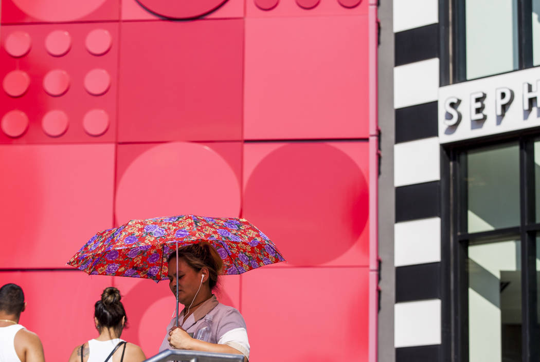 A pedestrian walks by the Miarcle Mile shops using a sun umbrella on the Las Vegas Strip as the temperature reached 116 on Tuesday, June 20, 2017.  Patrick Connolly Las Vegas Review-Journal @PConnPie